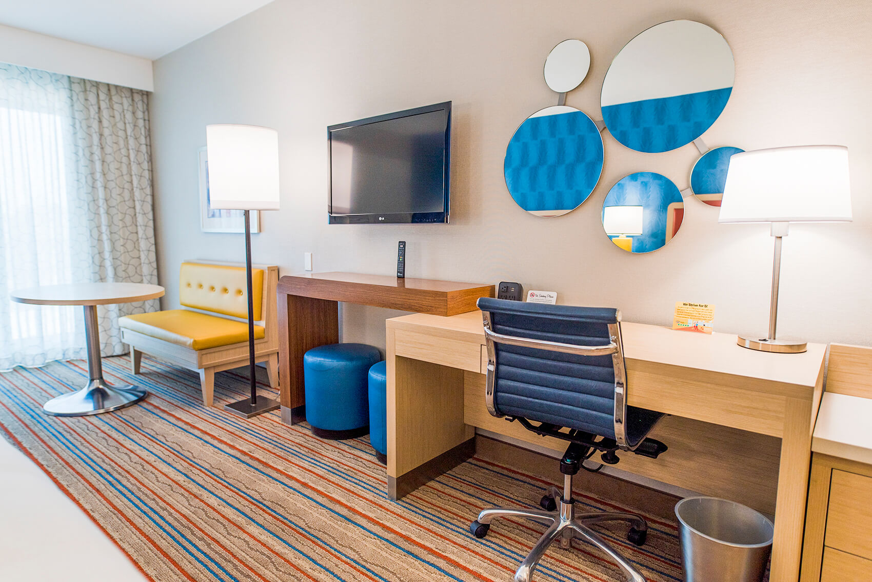 a hotel room with a desk, tv, table and bench