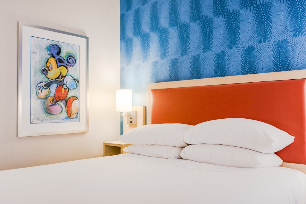 a hotel room pictured with a bed and Mickey Mouse picture on the wall