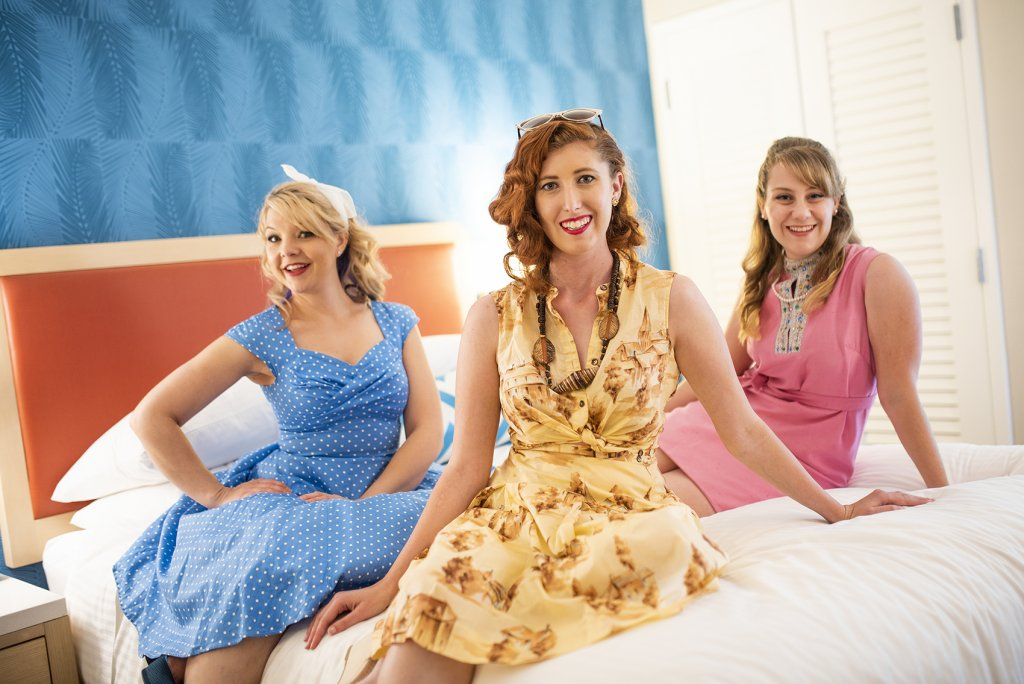 three women dressed in retro clothing sit on a bed in the new retro looking Howard Johnson Anaheim hotel rooms