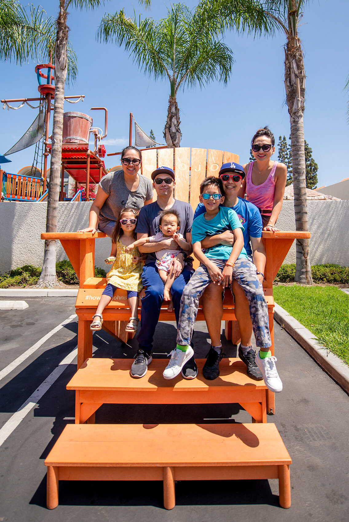 a family sits on the large orange Adirondack chair at Howard Johnson Anaheim