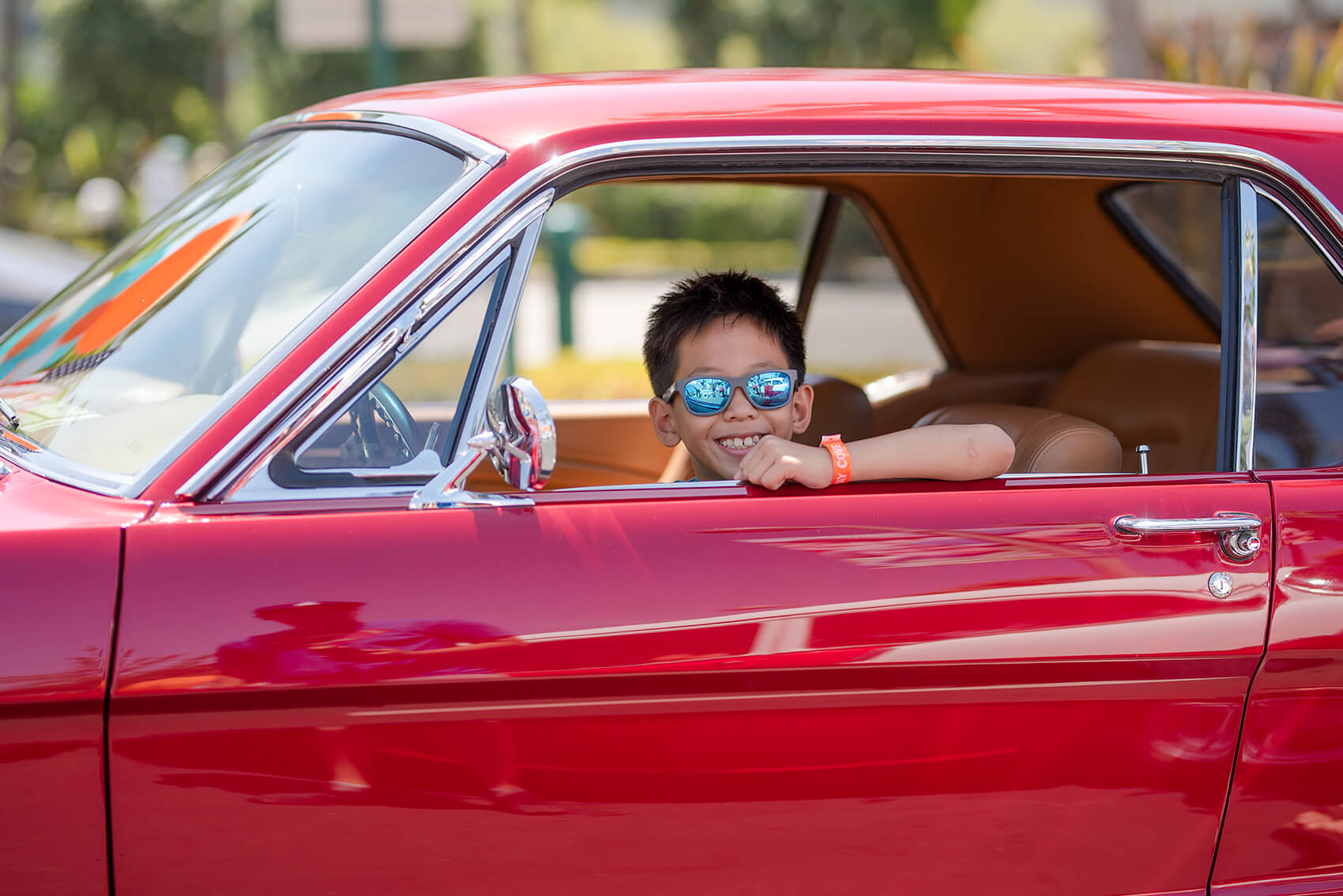 a child sits in the front seat of a retro red car and smiles