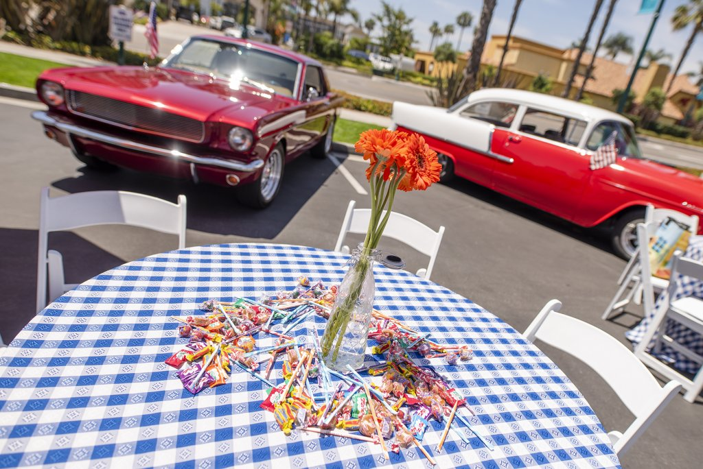 candy and flowers pictured on a table at the Howard Johnson Anaheim retro unveiling event near retro cars