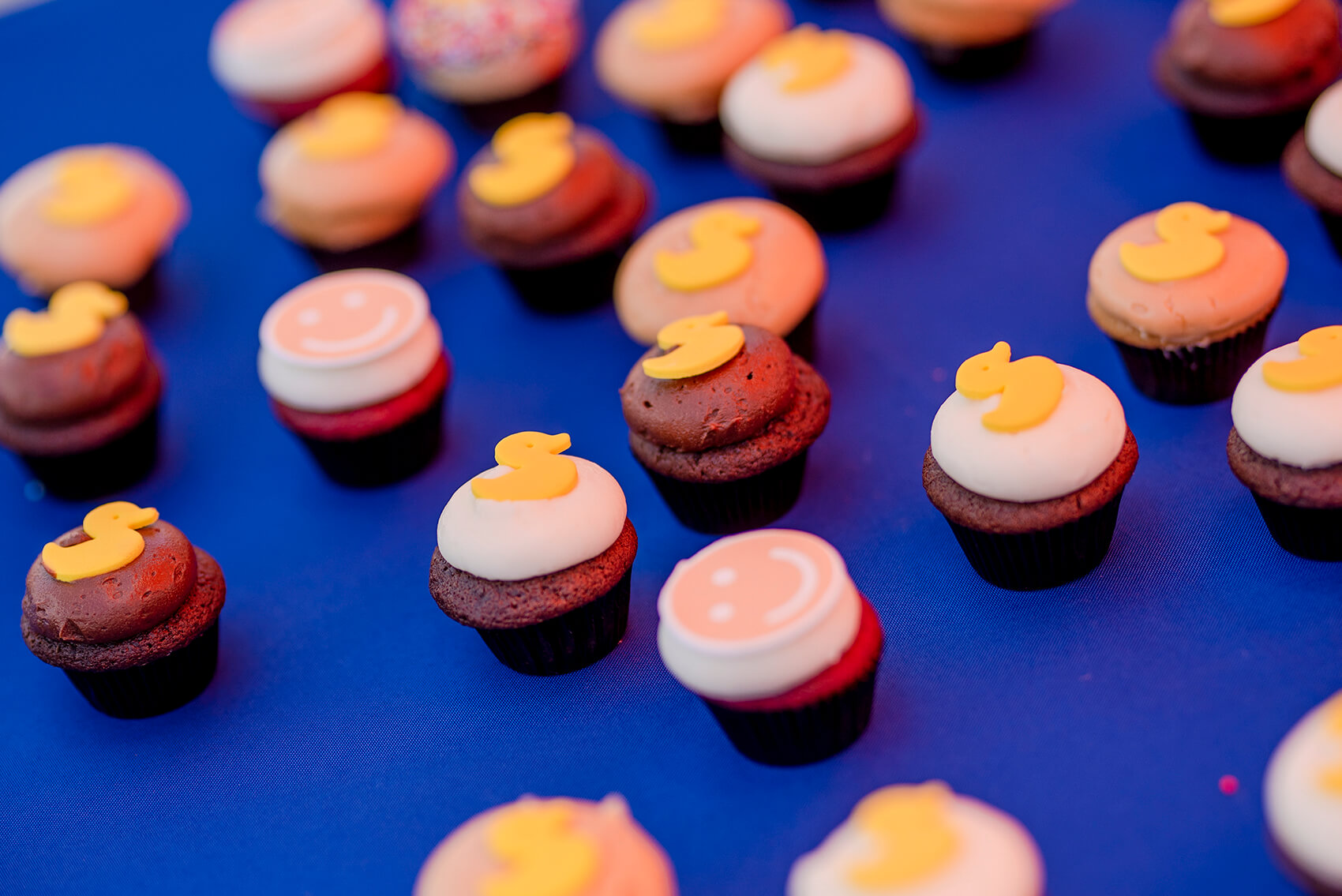 tiny cupcakes are decorated with smiles and rubber ducks