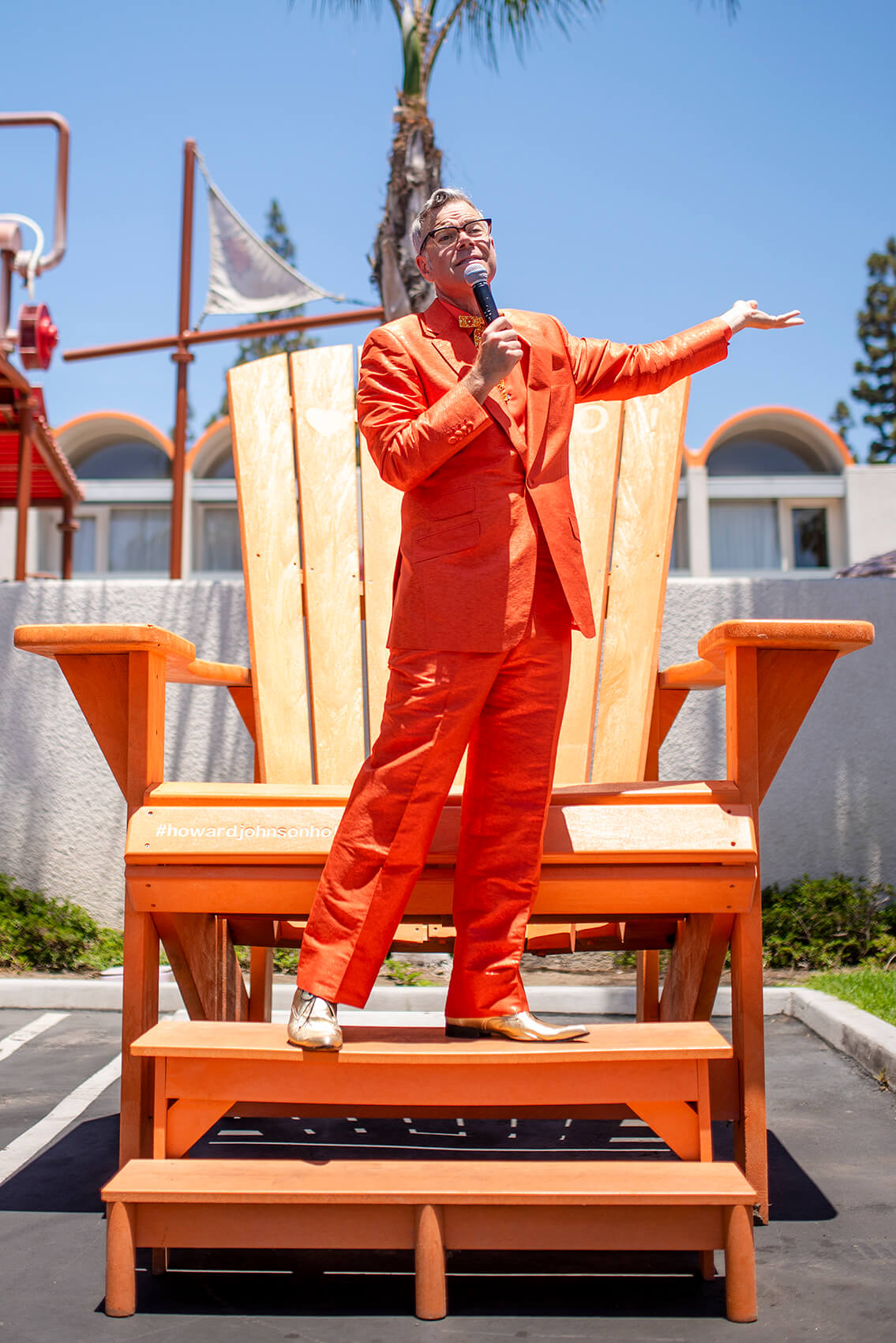 pop culture historian Charles Phoenix holds a microphone atop the large orange Adirondack chair at Howard Johnson Anaheim