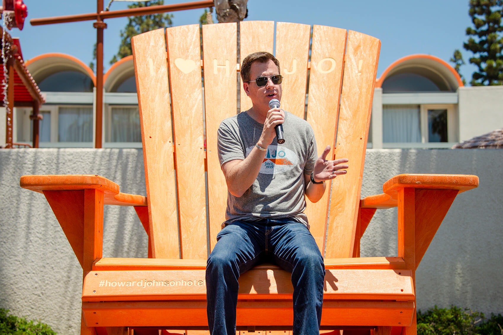 the General Manager of Howard Johnson Anaheim, Jonathan Whitehead, speaks into a microphone atop a giant orange beach chair