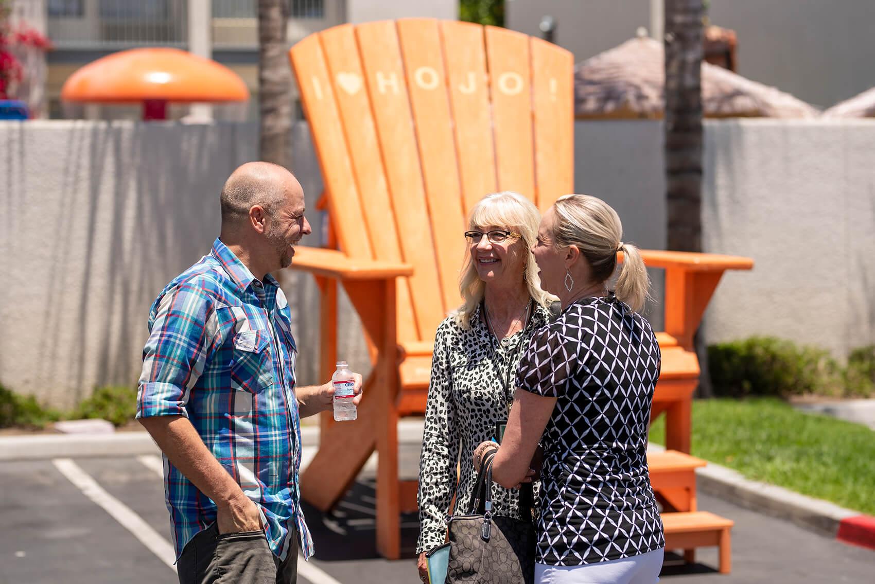 three adults talk at the Howard Johnson Anaheim retro re-do near the large orange Adirondack chair