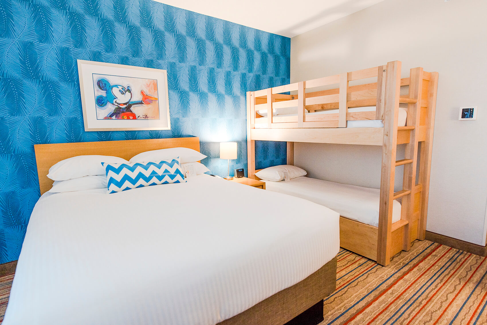 Mickey Mouse themed hotel room with a bed and bunk bed set