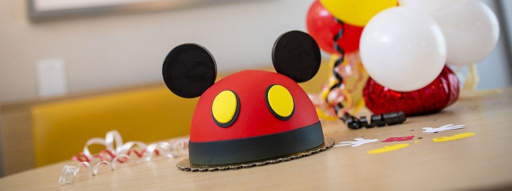 a Mickey Mouse cake with ears surrounded by balloons and confetti
