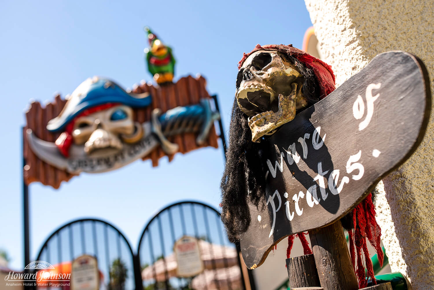 A closeup of skull and pirate decor, including a 'Beware of Pirates' sign and the Castaway Cove water playground sign at Howard Johnson Anaheim