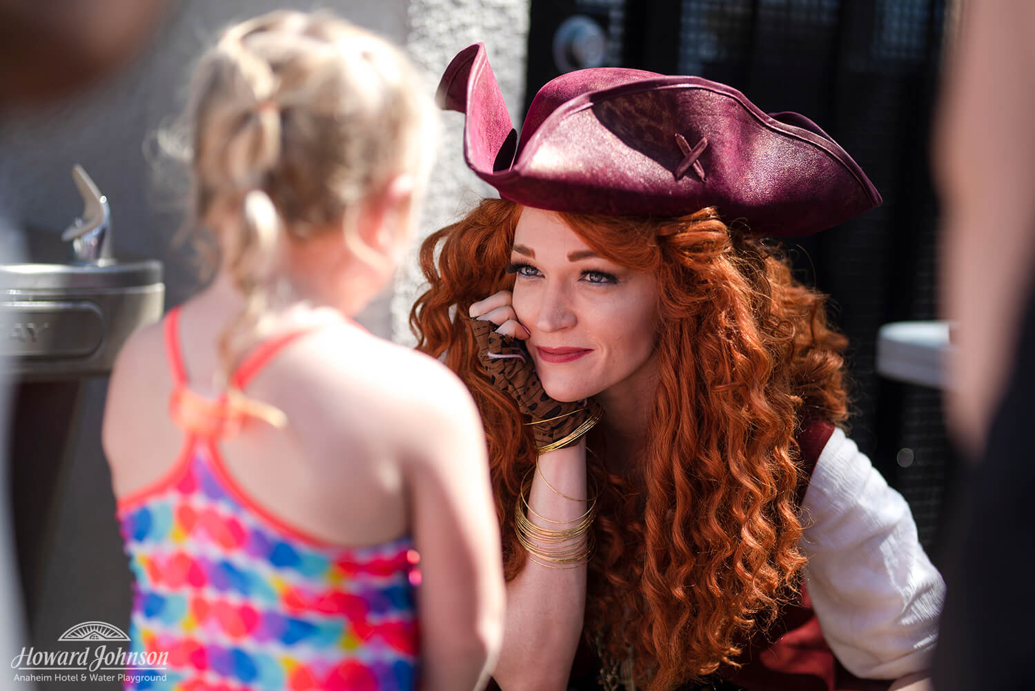 a woman dressed as a pirate smiles at a little girl