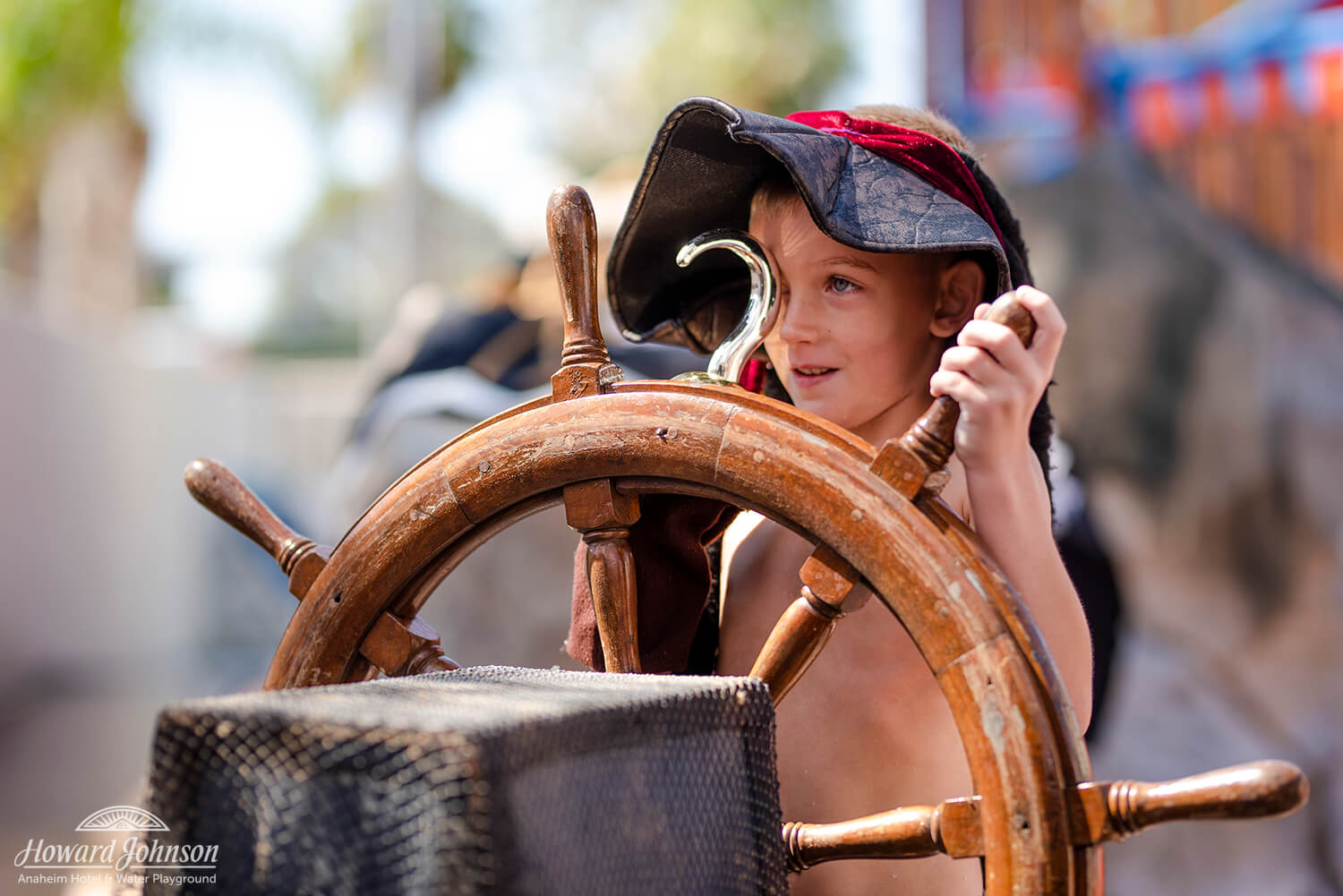 a little girl wearing a pirate hat with a gold hand hook mans the ship's wheel