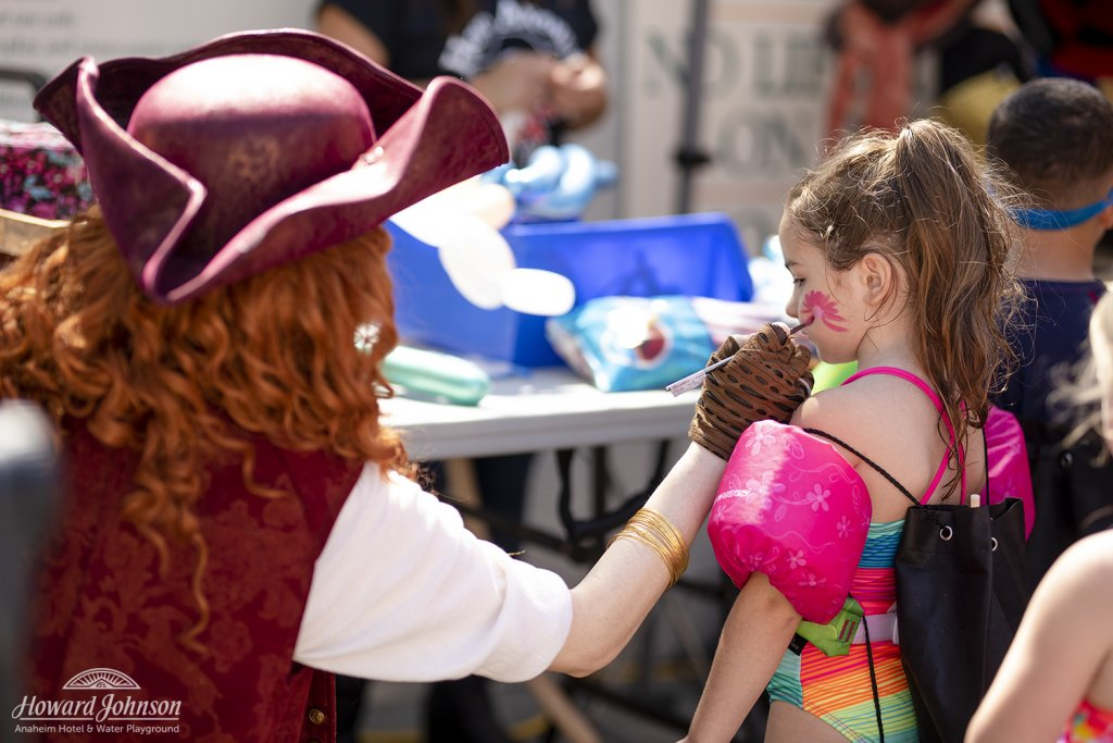 a woman dressed as a pirate paints on the face of a little girl