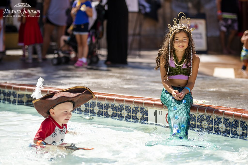 a little boy dressed as a pirate plays in the pool while a little girl dressed as a mermaid sits on the edge and smiles