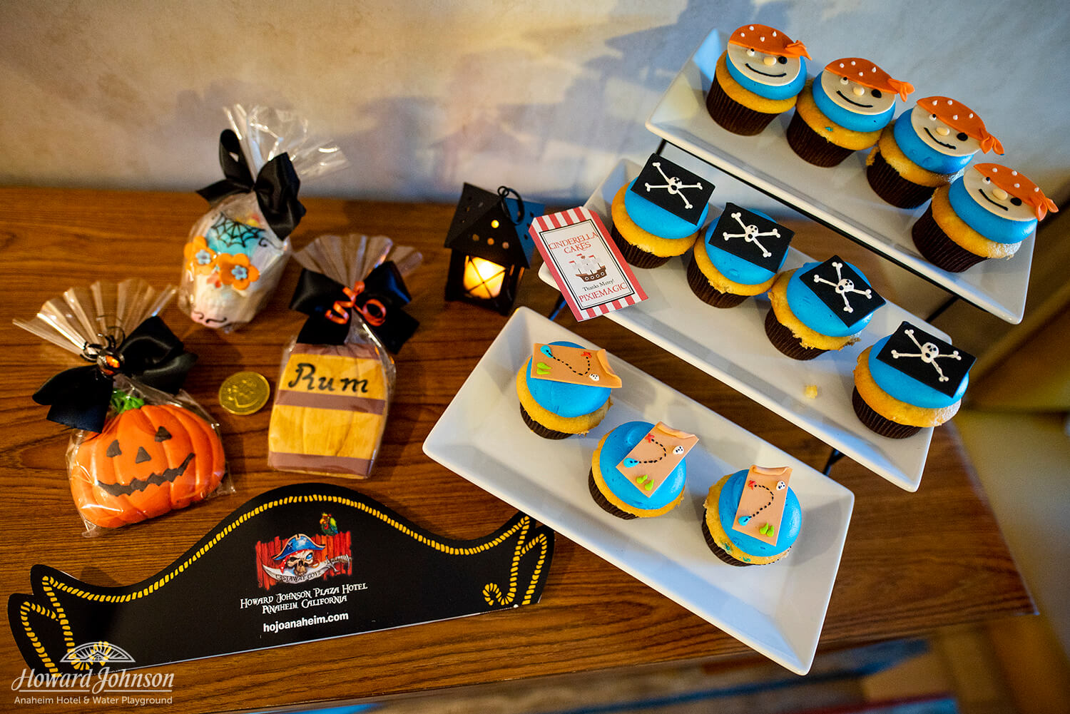 a collection of pirate and halloween themed cookies and cupcakes lay on a table