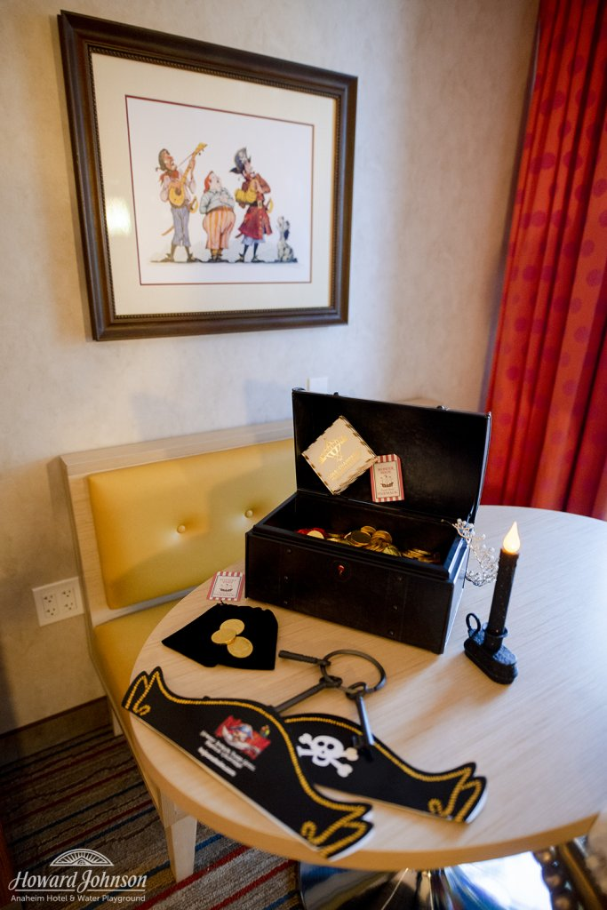 pirate themed accessories, including a hat, keys, candle, and treasure chest, lay on a table in a hotel room