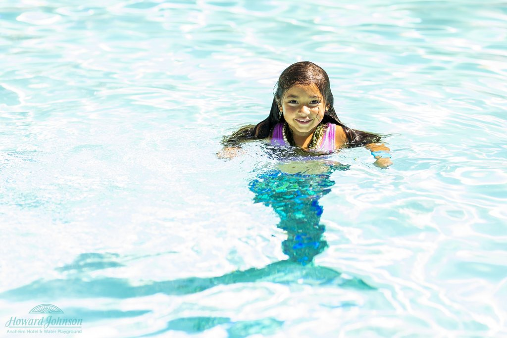 a little girl with a mermaid tail swims in the pool