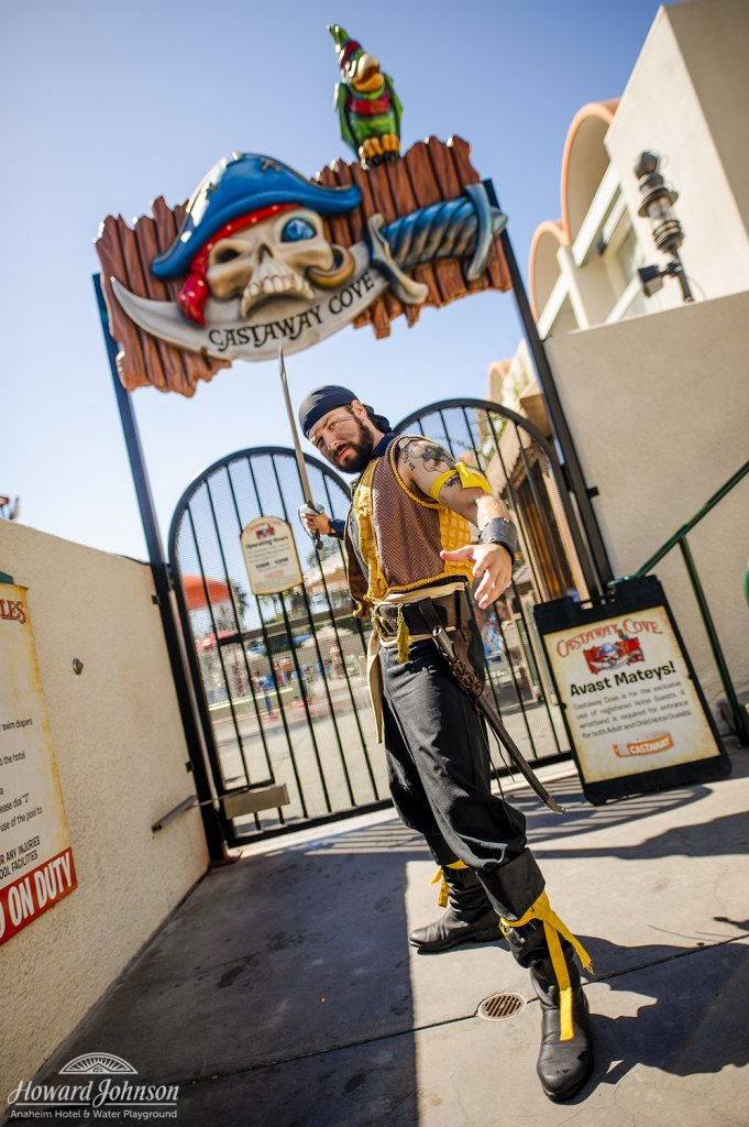 a man dressed as a pirate poses for a picture in front of the entrance to Castaway Cove