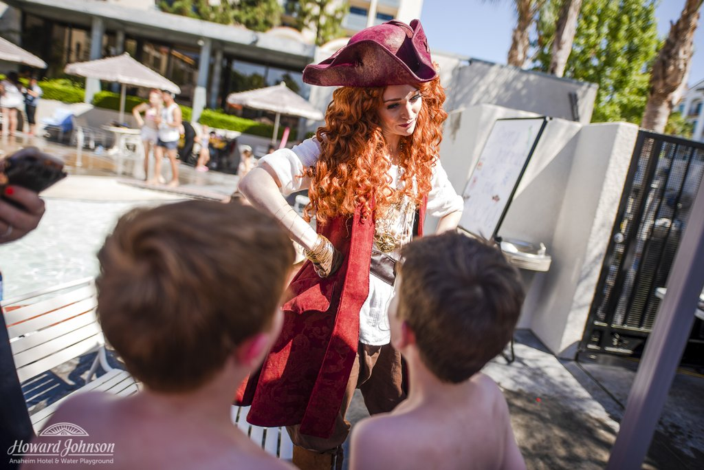 two young boys talk to a woman dressed like a pirate