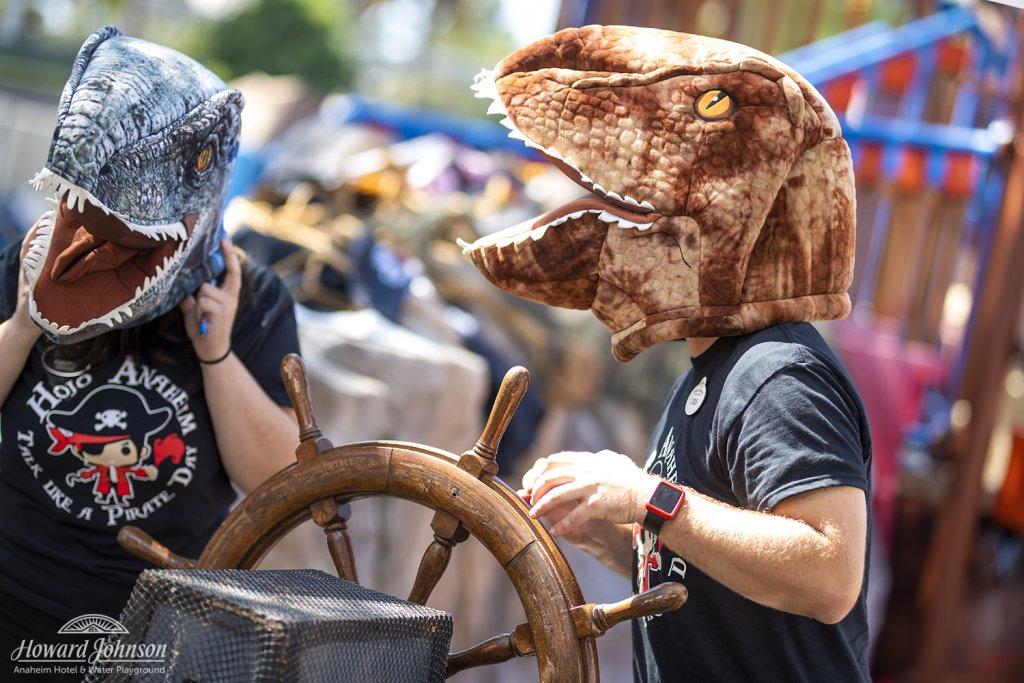 two men wear dinosaur heads over their heads