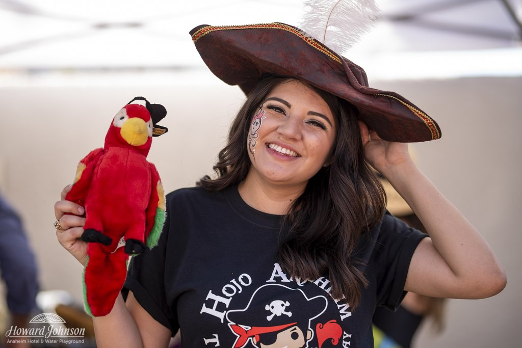 a woman smiles with a stuffed parrot and pirate hat on her head