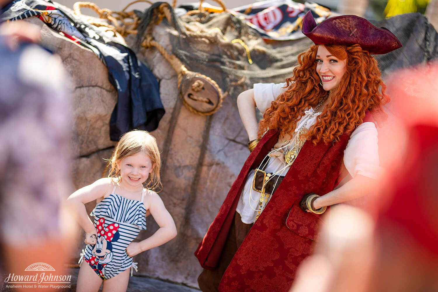 a little girl in a swimsuit poses for a picture with a woman dressed as a pirate