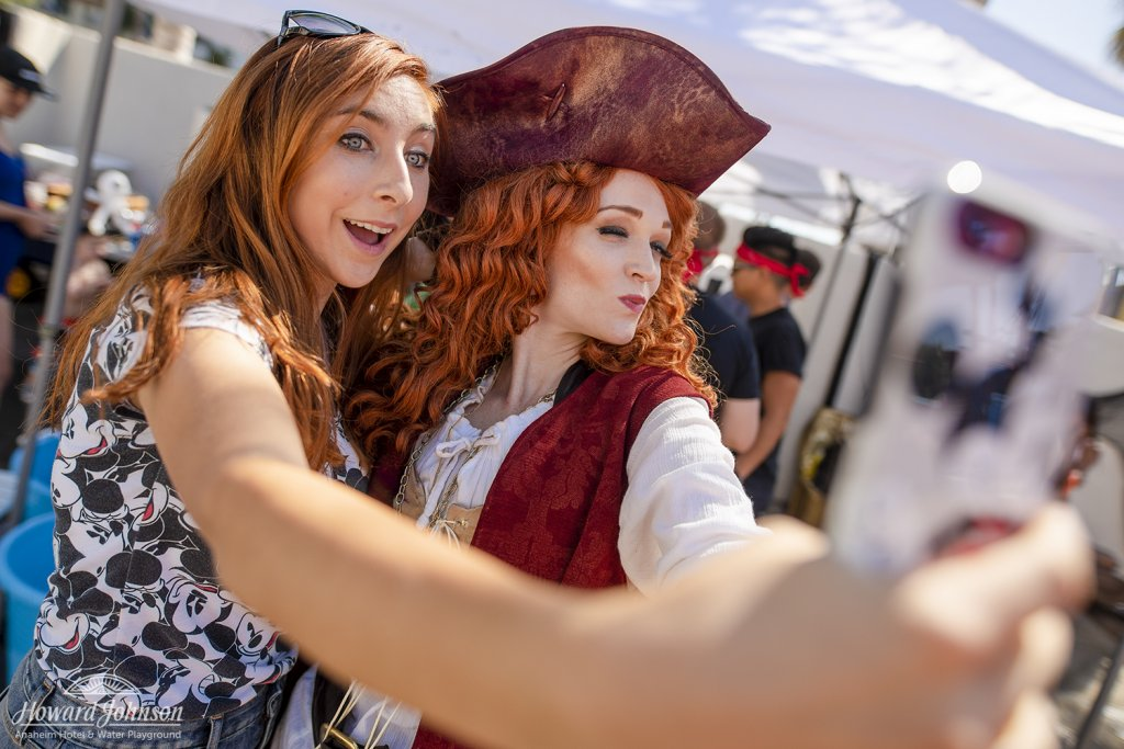 a woman takes a selfie with a woman dressed as a pirate