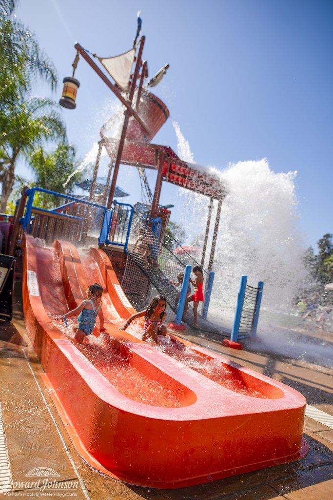 two children slide down a slide at Castaway Cove