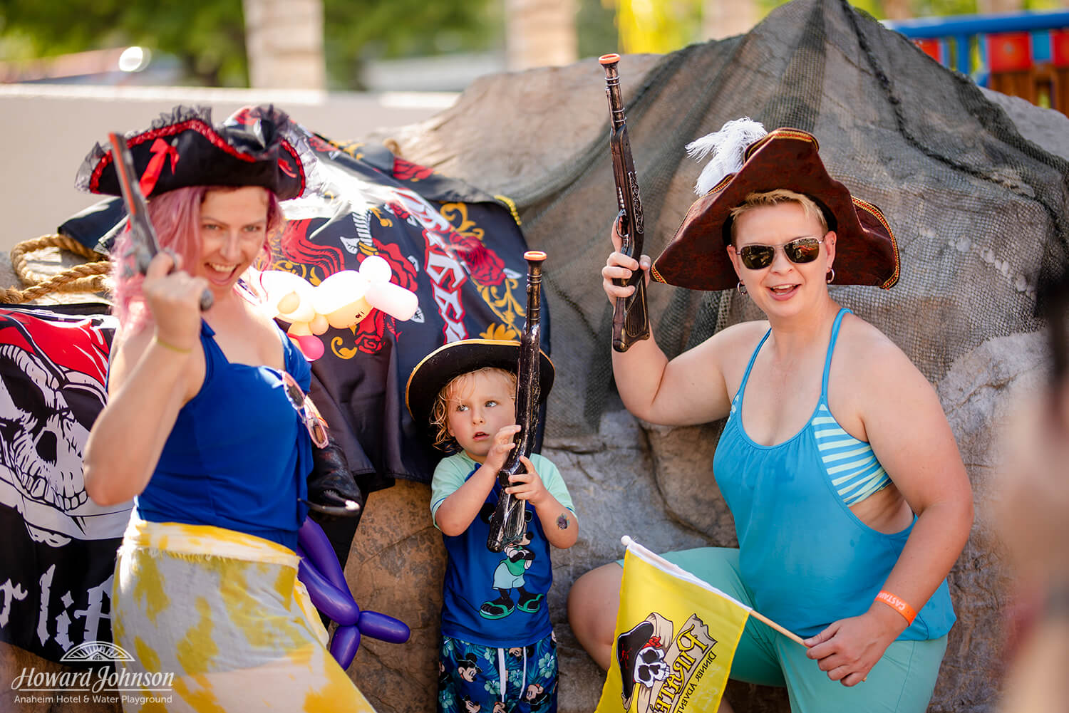 two women and a little boy pose with toy guns and pirate hats for a photo