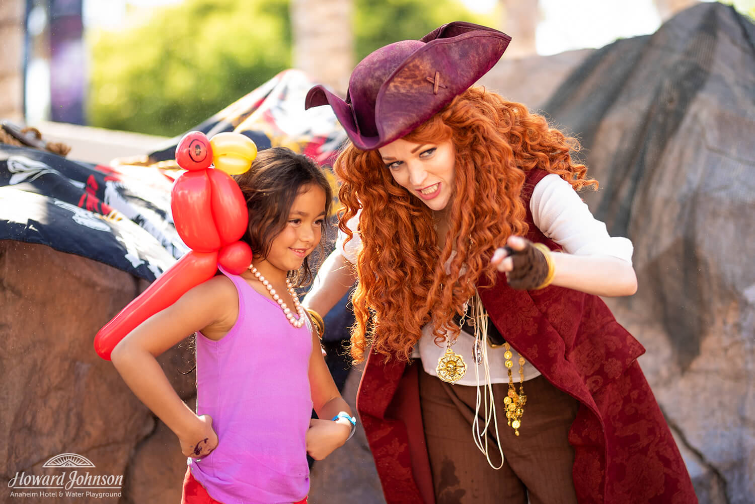 A little girl wearing an inflatable parrot on her shoulder poses for a picture with a woman in a pirate costume