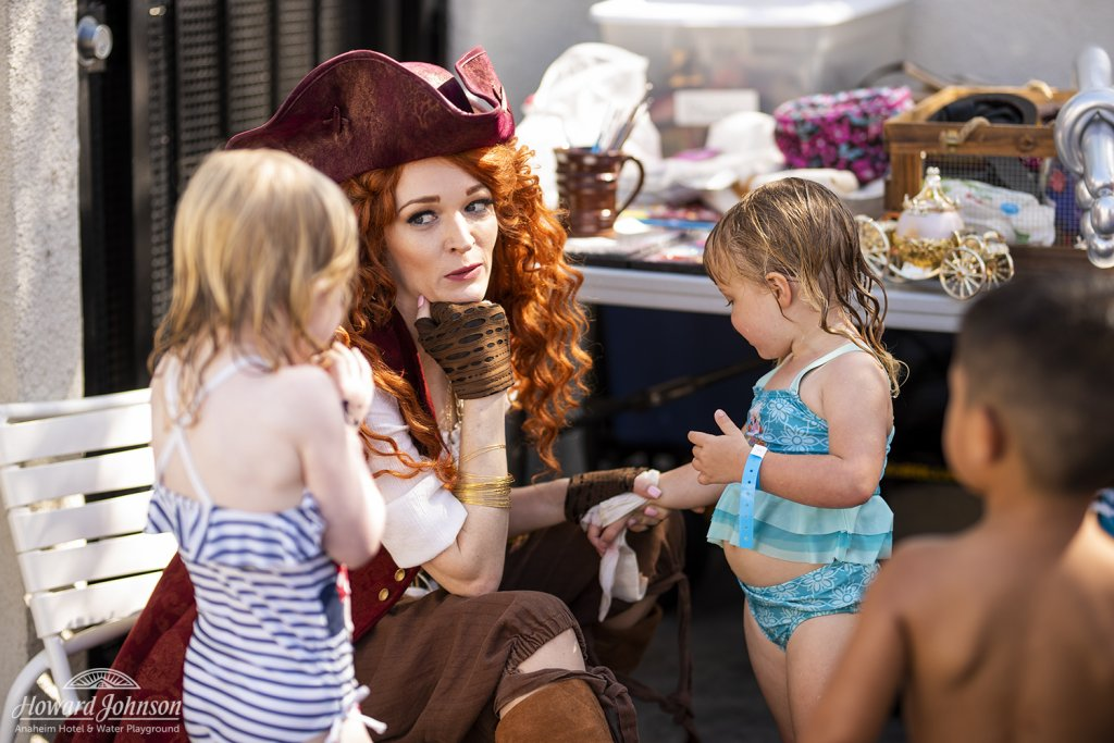 two little girls in swimsuits talk to a woman dressed in a pirate costume at Castaway Cove