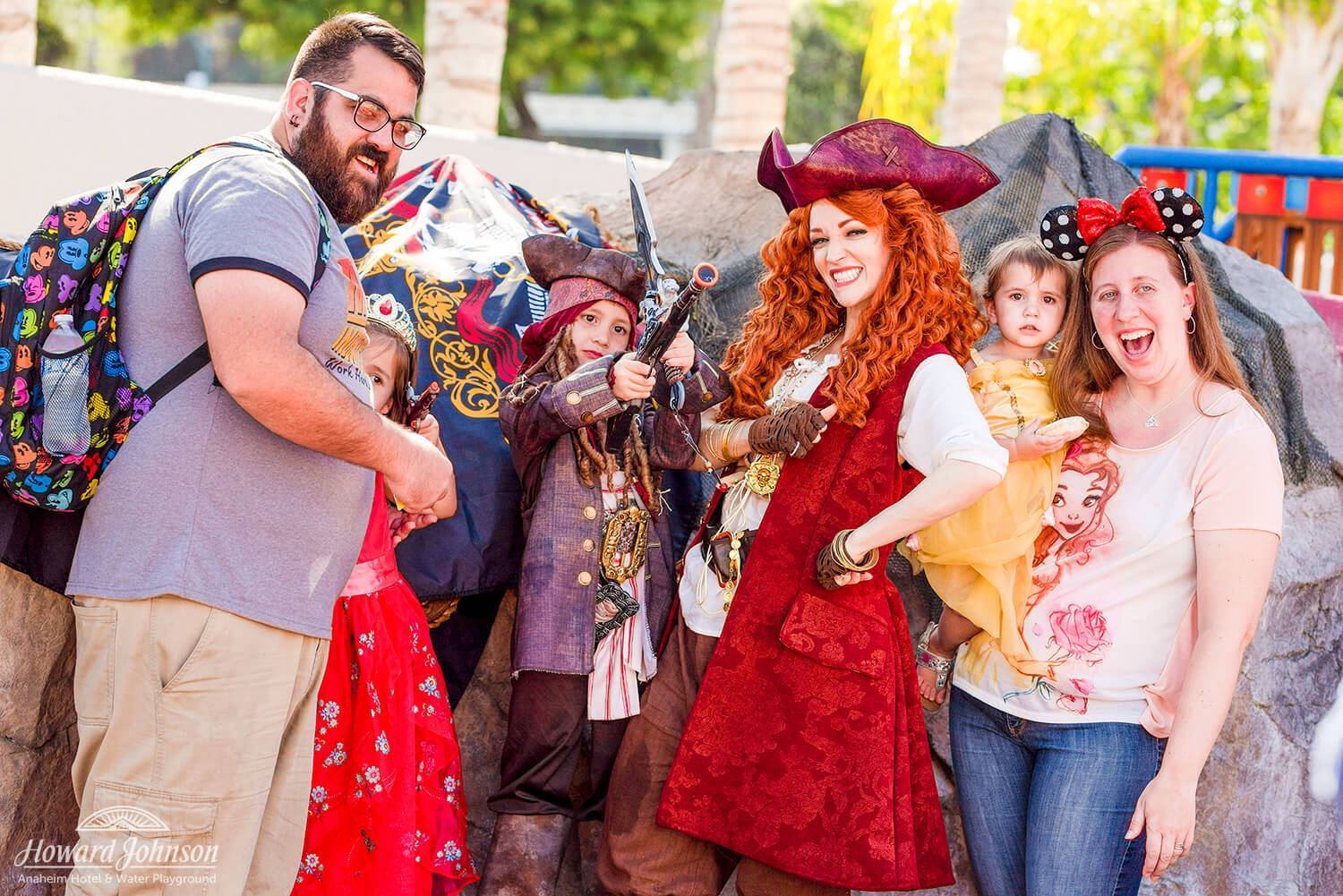 a family dressed in Disney gear poses with a woman dressed in a pirate costume