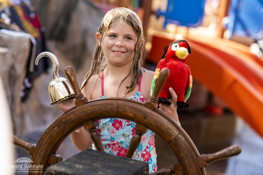 a little girl with a gold hand hook and parrot mans the ship's wheel at Castaway Cove