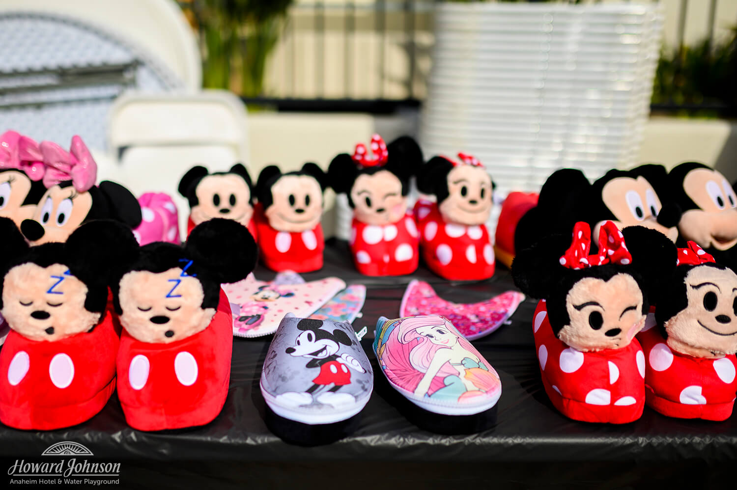 Minnie and Mickey Mouse slippers and shoes are displayed on a table