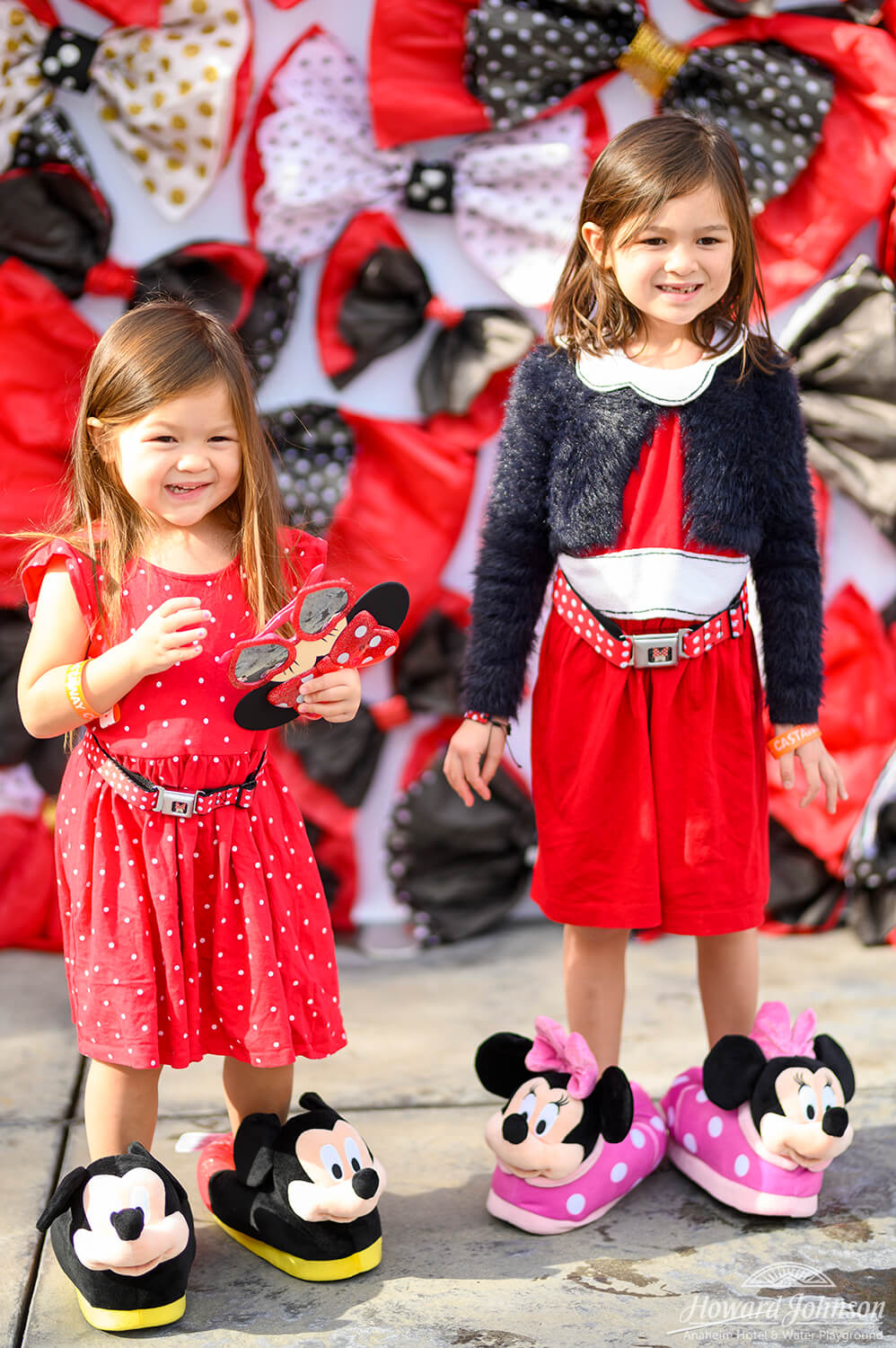 two little girls wear Mickey and Minnie Mouse slippers while smiling in front of a backdrop of polka dot bows