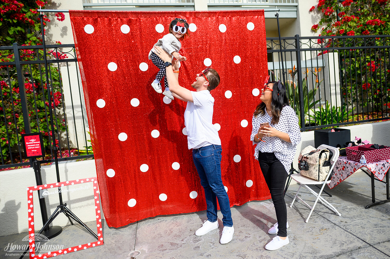 a man holds a little girl in the air in front of a polka dot backdrop while a woman smiles and watches them