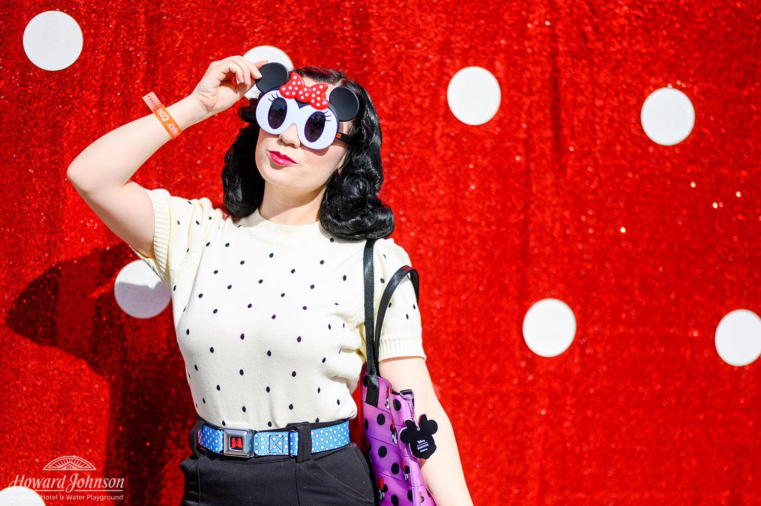 A young woman poses for a picture in front of a polka dot backdrop wearing Minnie Mouse sunglasses