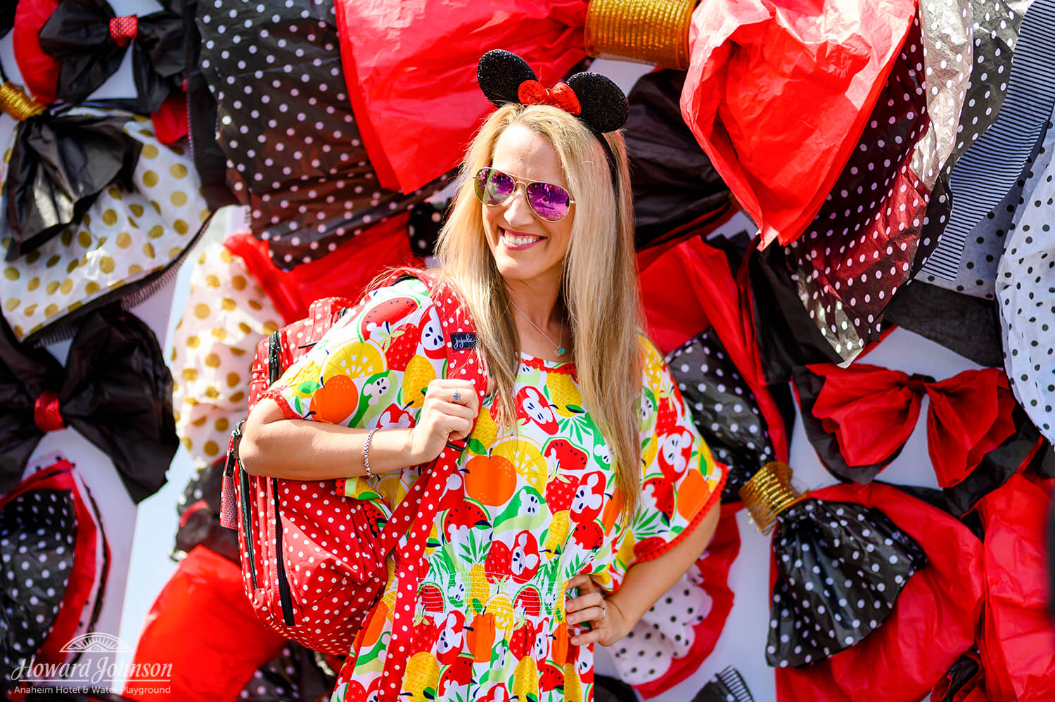 a woman poses for a picture while holding a polka dot backpack in front of a backdrop of polka dot bows