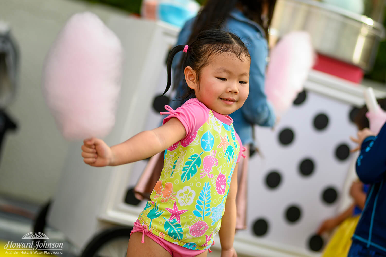 a little girl wearing a swimsuit holds pink cotton candy in her hand