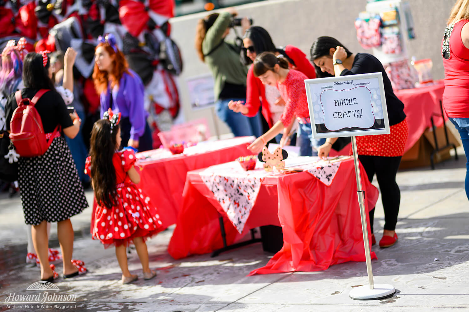 """women set up tables labeled from a sign, """"Minnie crafts!"""" as a young girl in a Minnie Mouse polka dot dress watches"""