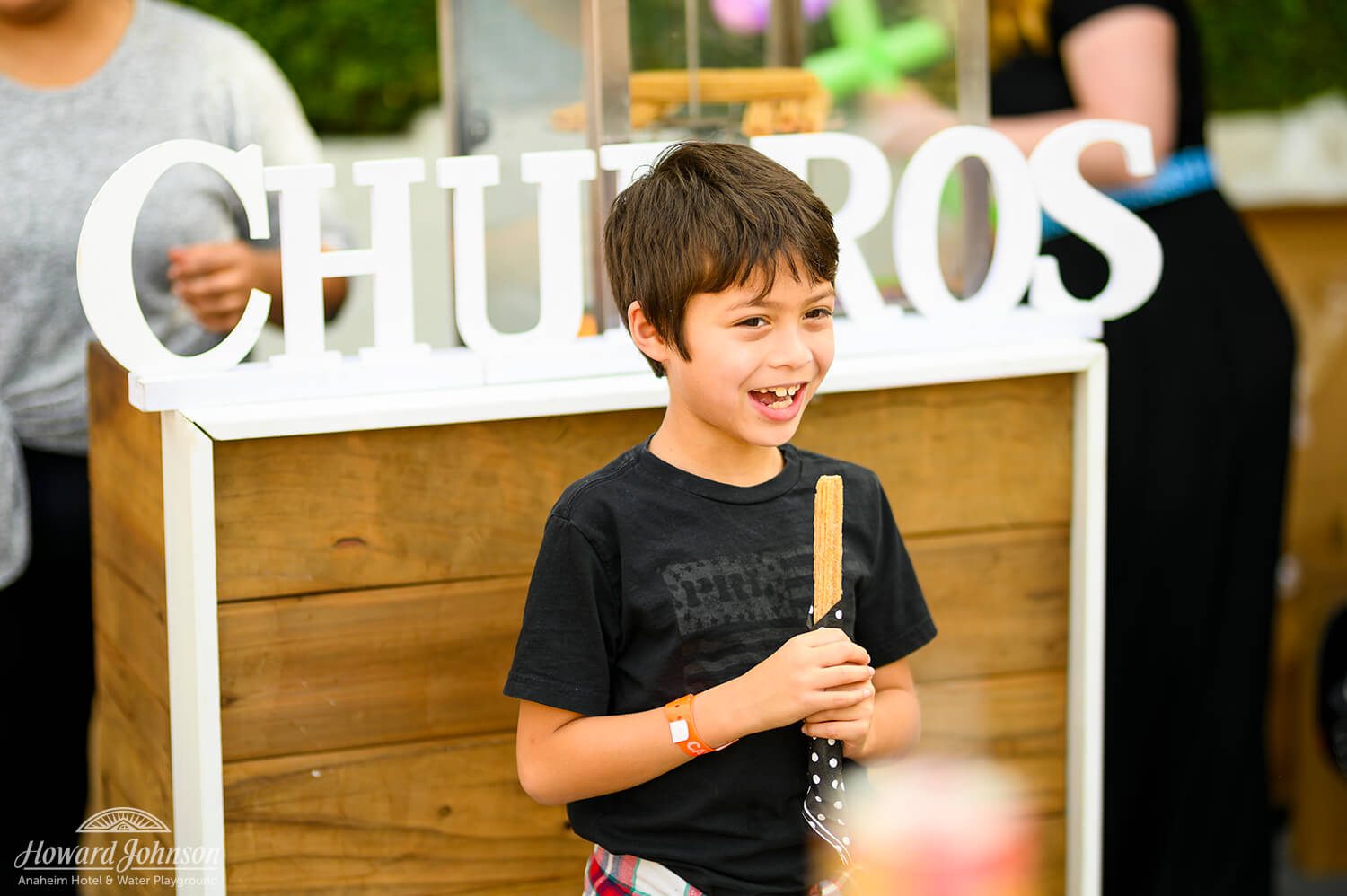 A young boy smiles with a churro in his hand in front of a sign for churros