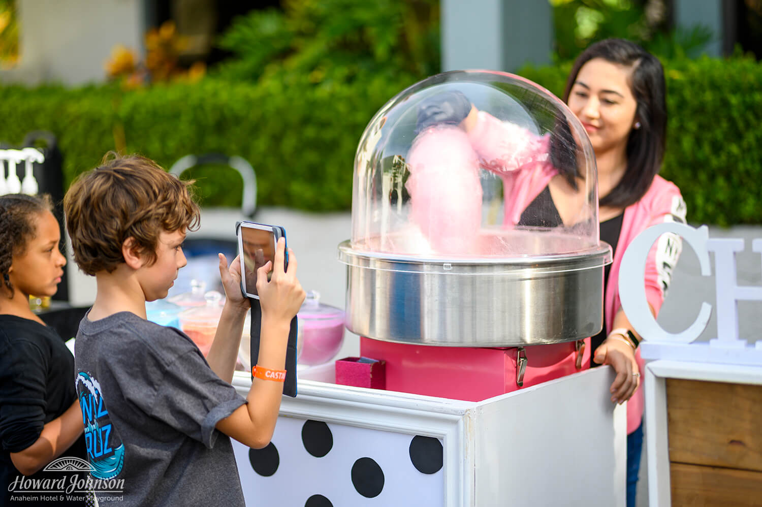 a young woman makes pink cotton candy for two children from a machine while one child takes a photo of it