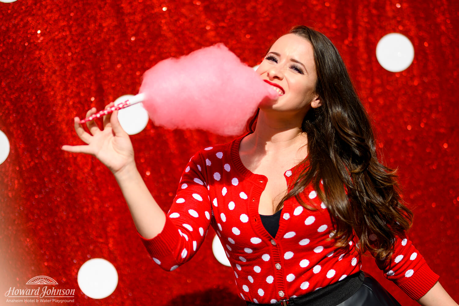 A young woman wearing a polka dot sweater poses in front of a polka dot picture background with pink cotton candy in her mouth