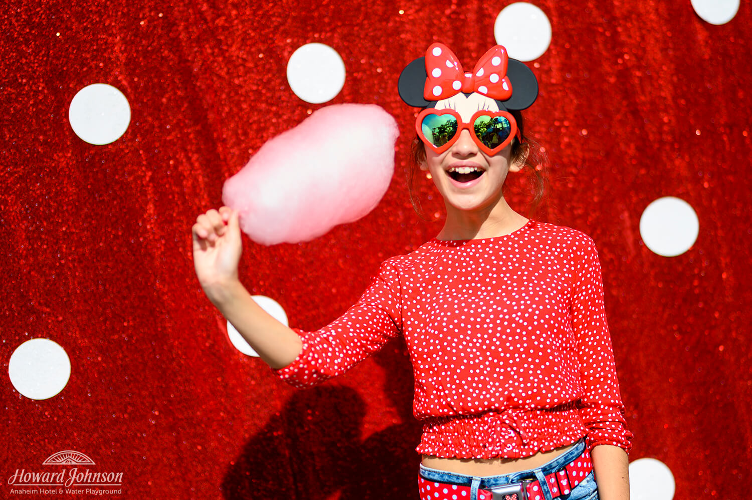 a young girl poses in Disney sunglasses and a polka dot shirt in front of a polka dot picture background with pink cotton candy in her hand