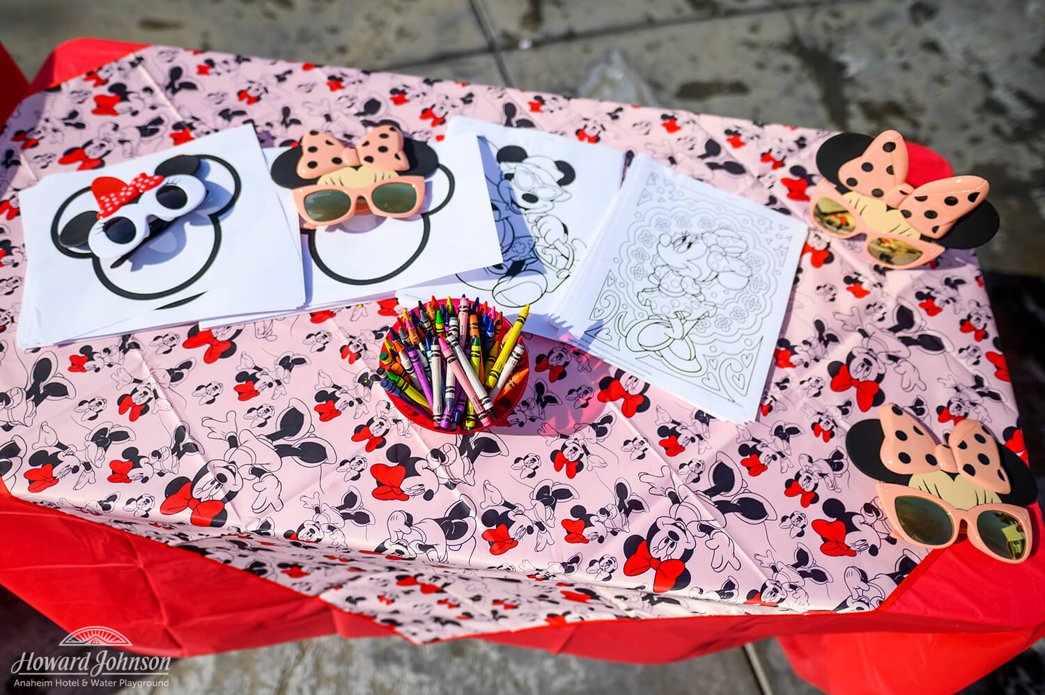 Minnie Mouse coloring pages, sunglasses, and crayons are pictured on a Minnie themed craft table