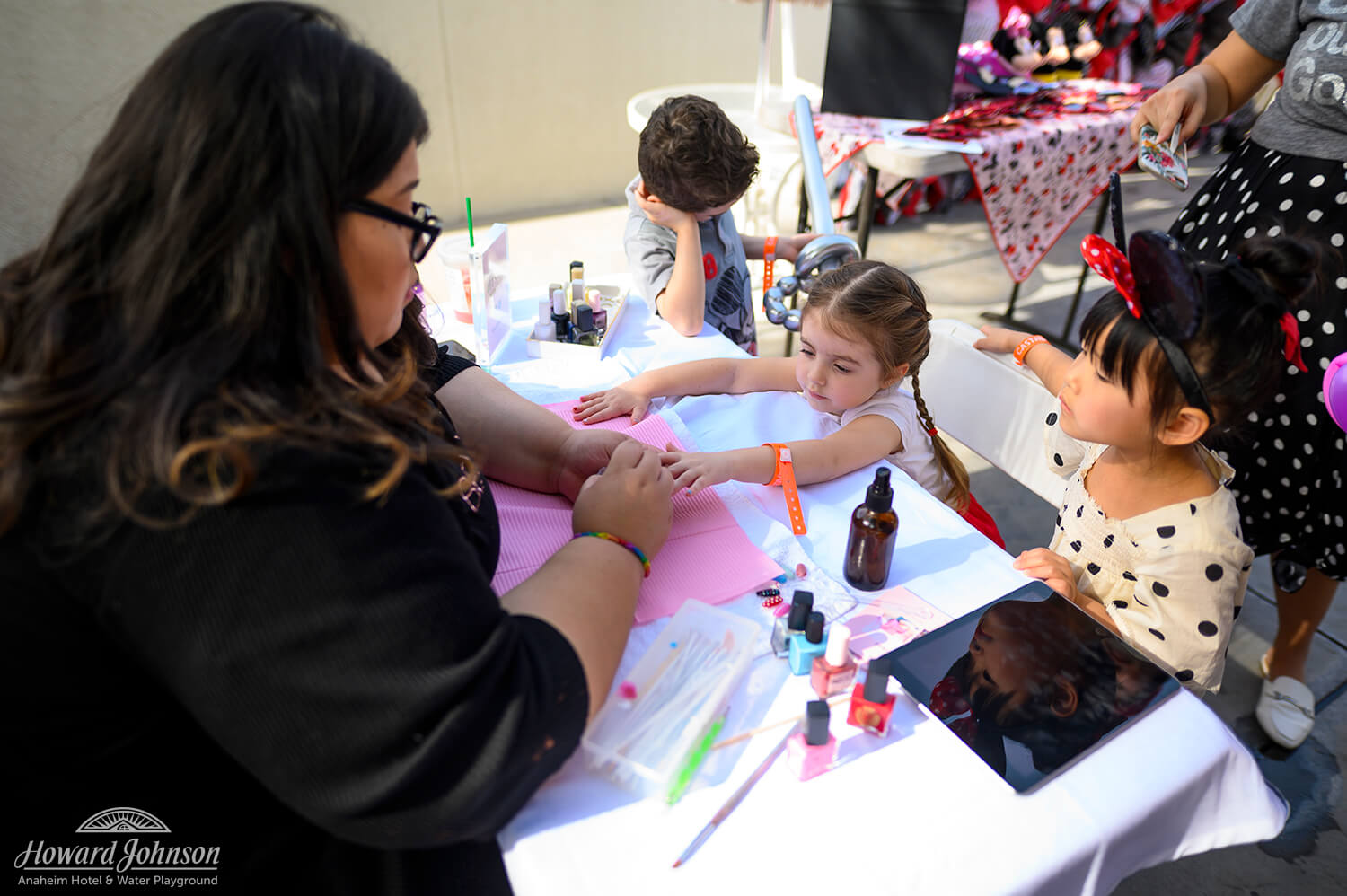 a woman paints the nails of a young girl while her friend watches at the table