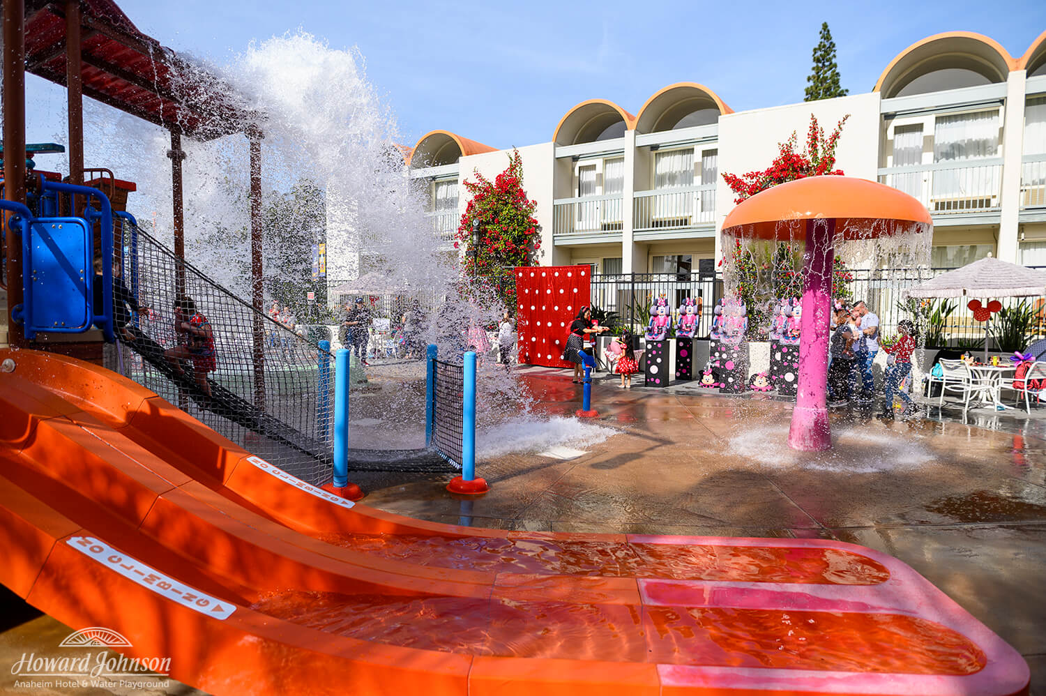 a wide shot of children and parents playing at the water playground at the Howard Johnson Anaheim hotel