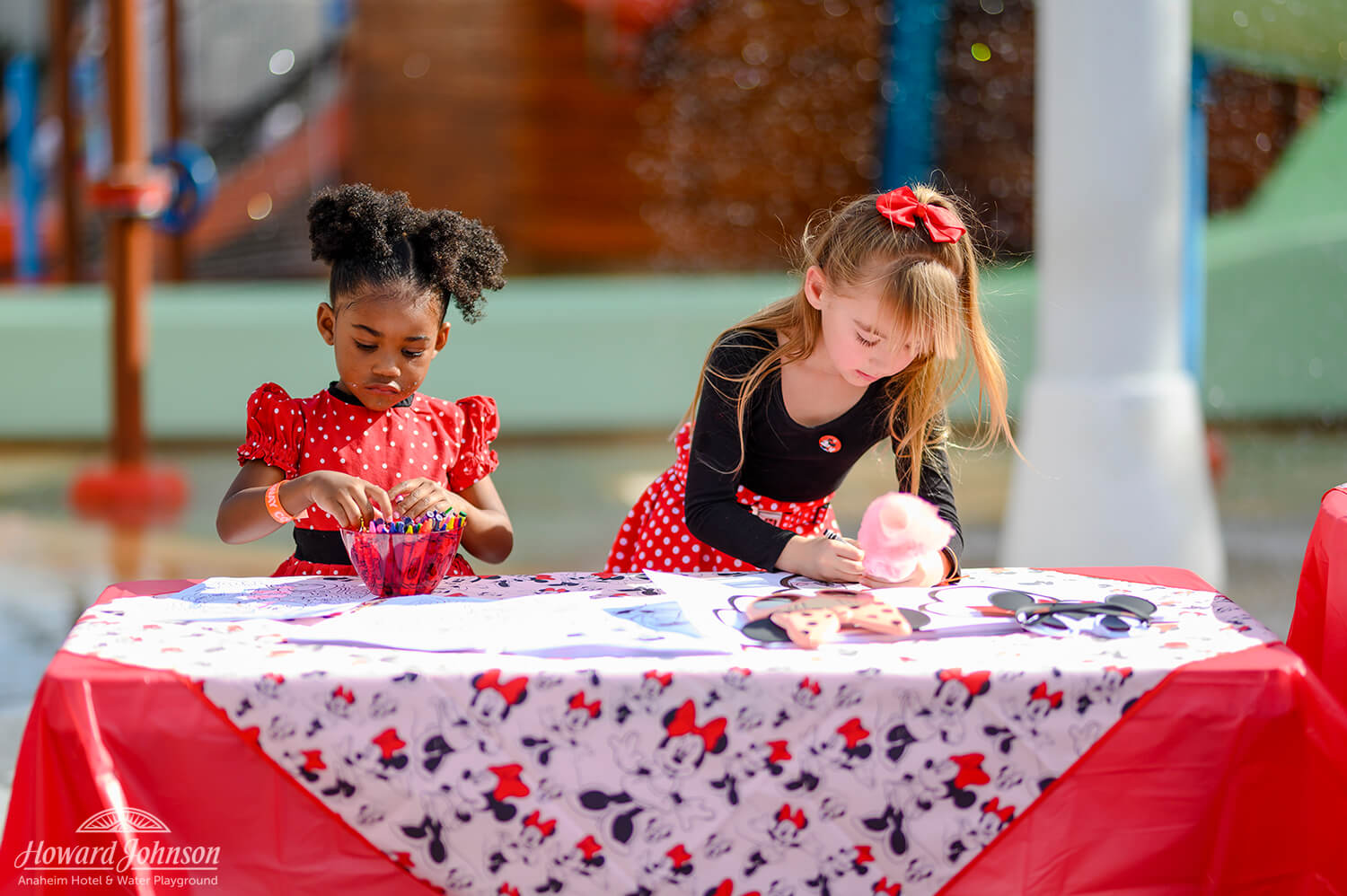 Two young girls color with crayons on a Minnie Mouse craft table