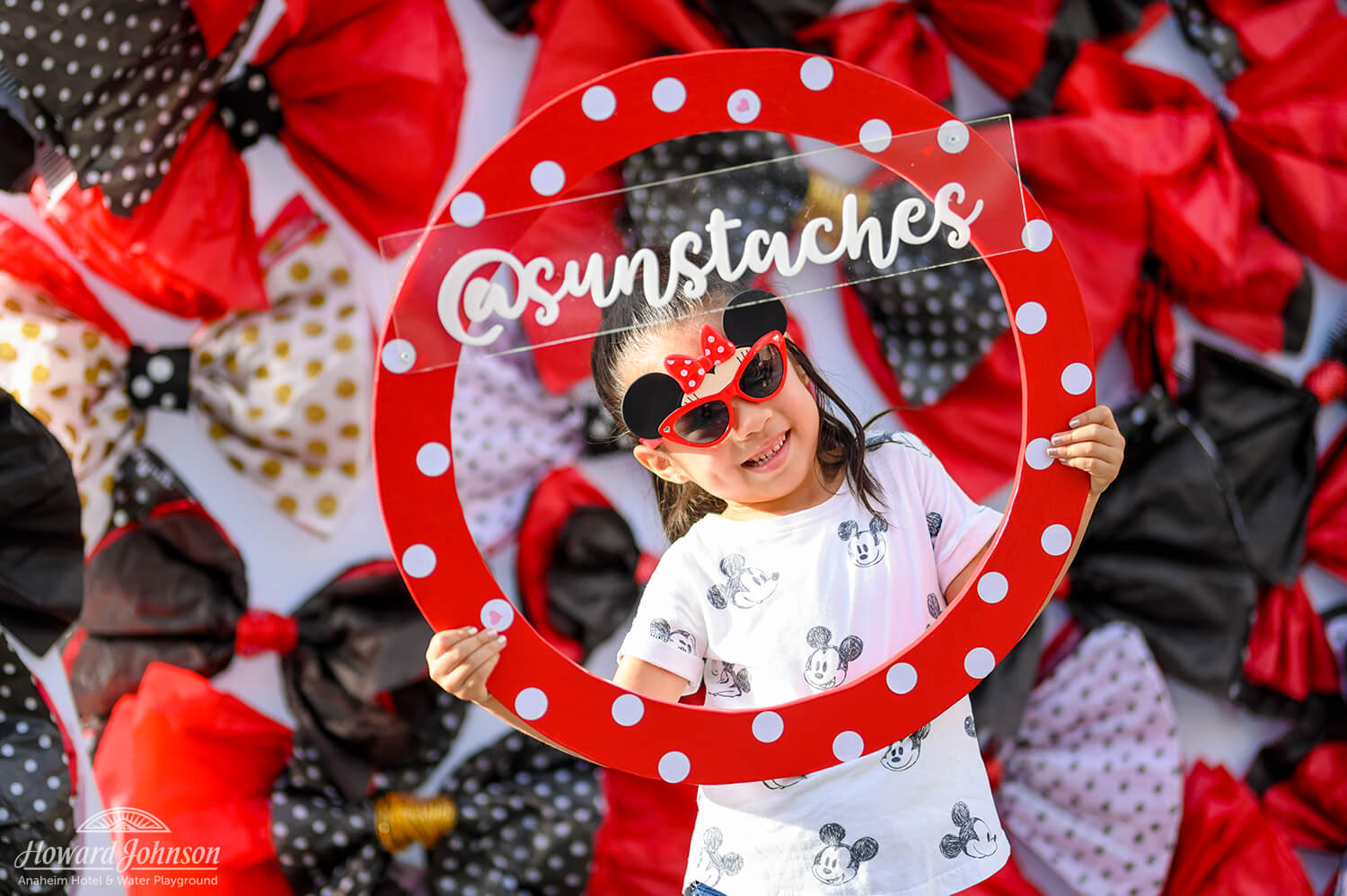 a little girl with Minnie Mouse sunglasses poses for a photo with a circular polka dot frame and social media handle on it