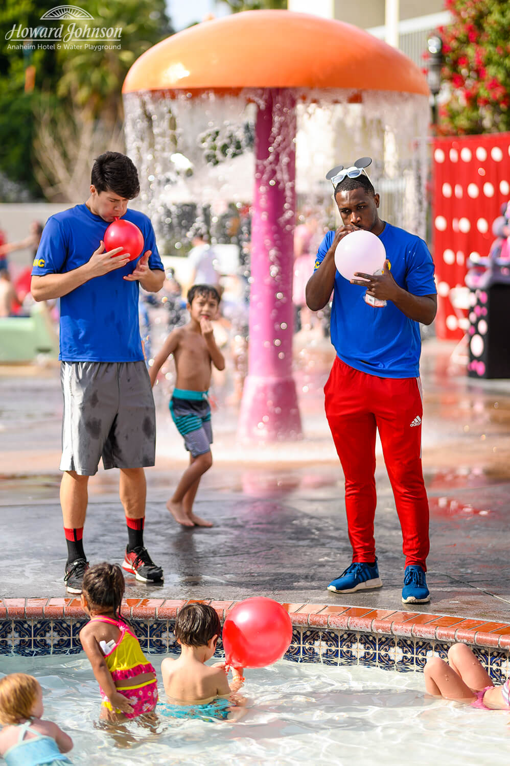 two men blow up balloons near a pool at Howard Johnson Anaheim hotel as children watch on and play in the pool