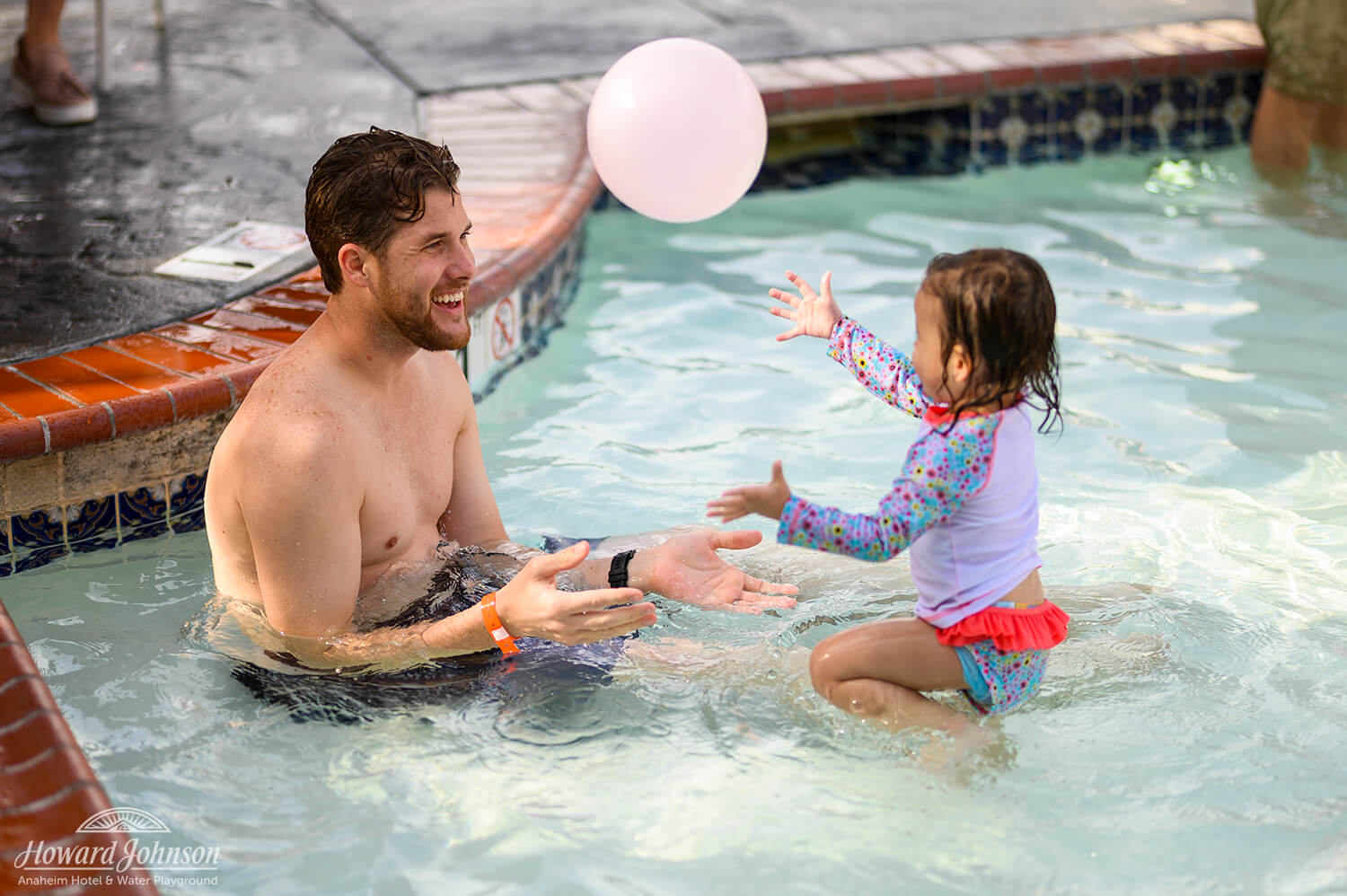 a man and a small girl play with a pink balloon in the air while in the pool